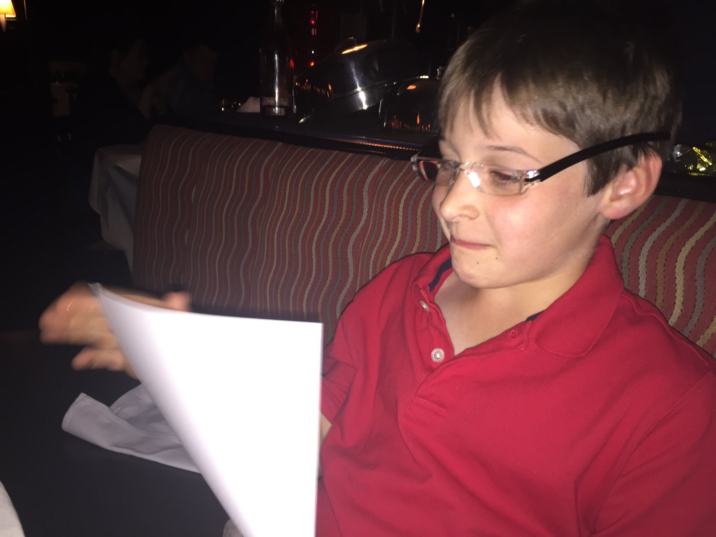 Mr. Belle reviewing a manuscript over a working dinner.