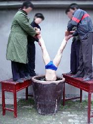 法輪功學員演示山東濰坊勞教所迫害酷刑:扒光衣服(一絲不挂)抬進廁所,將頭部插入盛滿水的大水缸裡灌,灌幾分鐘,提上來,仍不轉化就再灌……(明慧網)