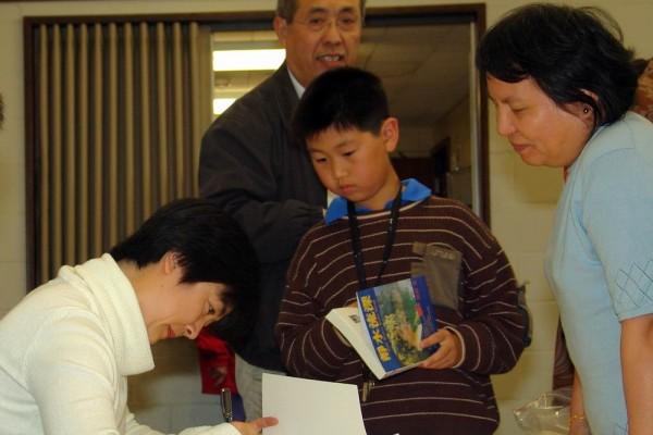 圖為3月25日曾錚在墨爾本新書發佈會期間為讀者簽名。(圖片來源:大紀元)