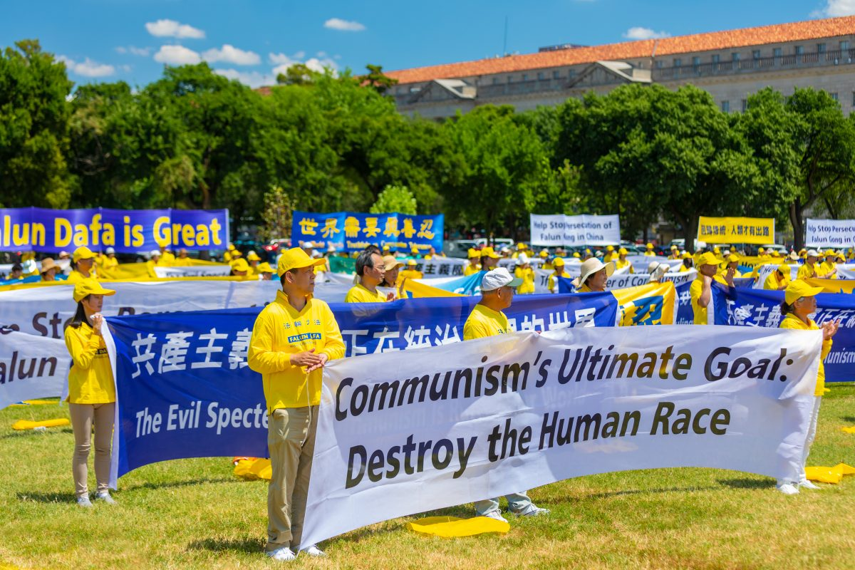 Falun Gong practitioners hold banners at a rally calling for an end to the persecution of Falun Gong, at the Washington Monument on July 19, 2018. (Mark Zou/Epoch Times)