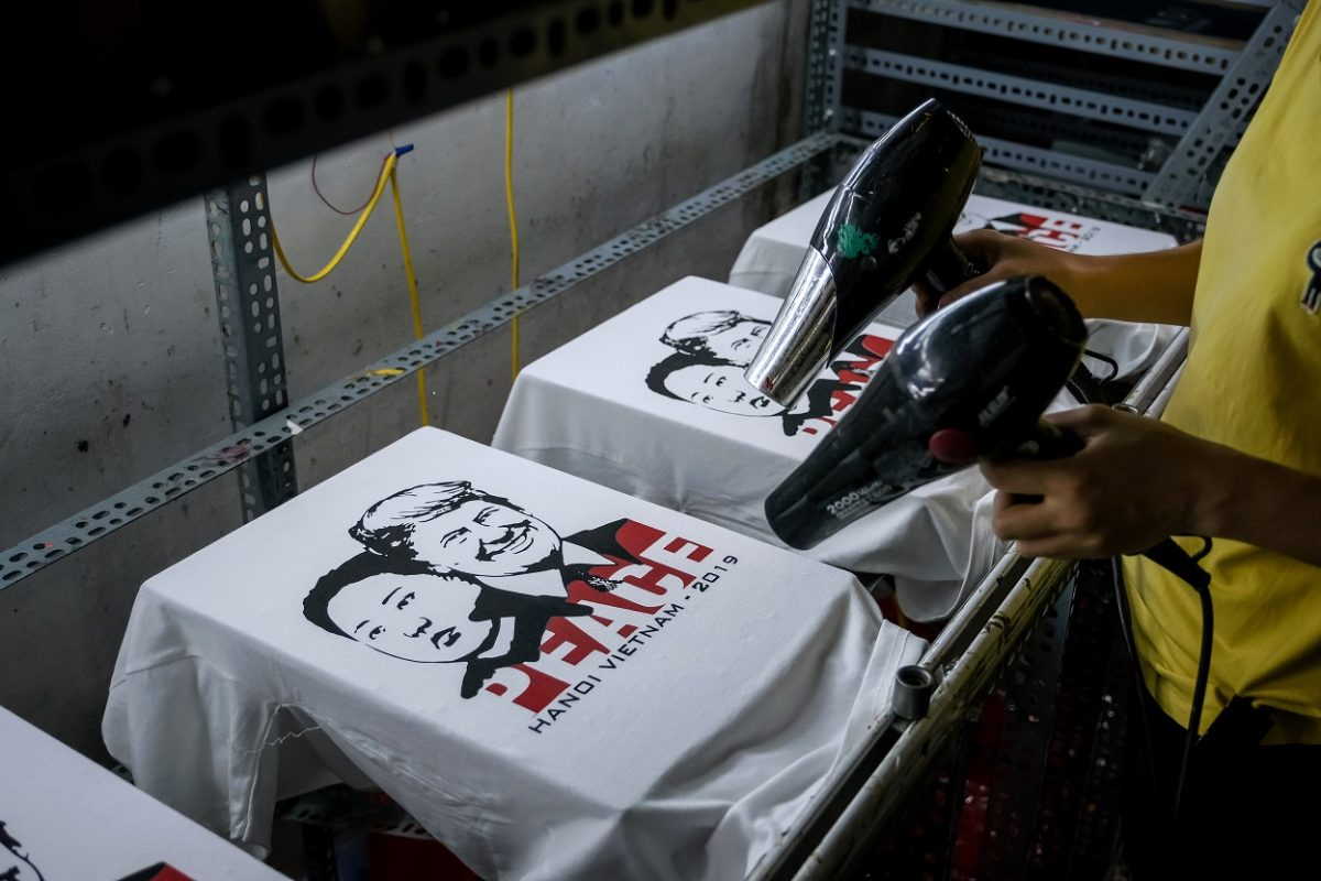 A worker at the t-shirt store of Truong Thanh Duc dry the newly printed t-shirts with the portraits of U.S. President Donald Trump and North Korean leader Kim Jong Un in Hanoi, Vietnam on Feb. 21, 2019. (Linh Pham/Getty Images)