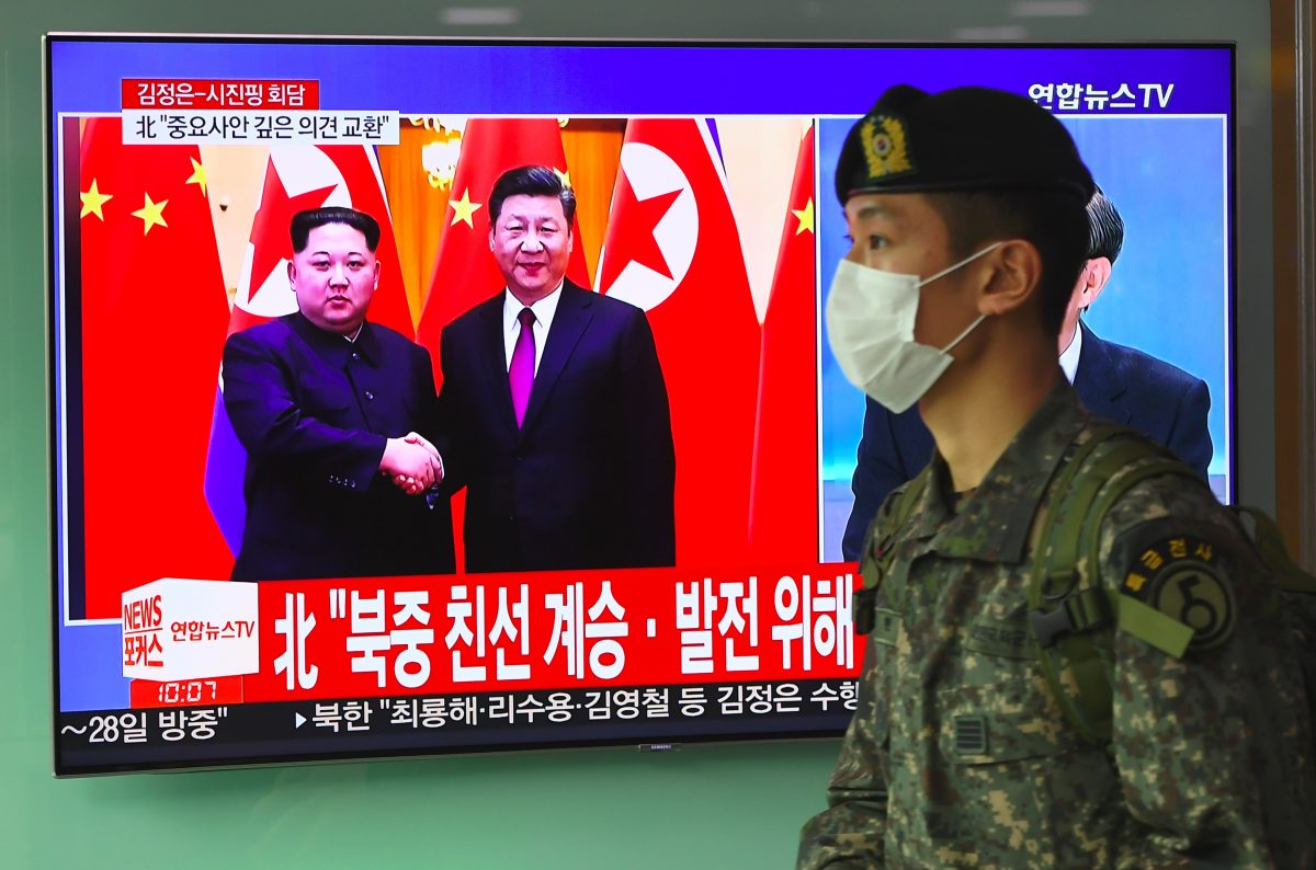 A South Korean soldier walks past a television news screen reporting about a visit to China by North Korean leader Kim Jong Un, pictured with Chinese leader Xi Jinping, at a railway station in Seoul on March 28, 2018. (JUNG YEON-JE/AFP/Getty Images)