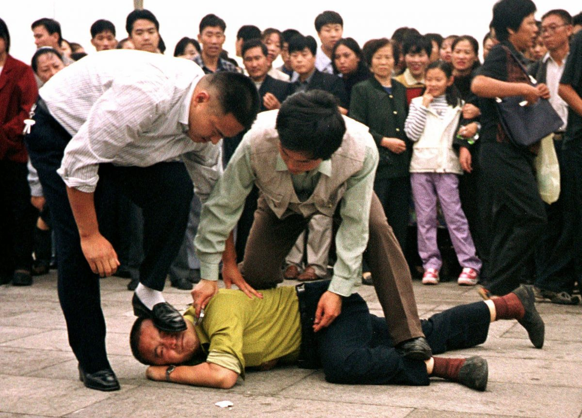 Police detain a Falun Gong protester in Tiananmen Square as a crowd watches in Beijing in this Oct. 1, 2000, photo. (AP Photo/Chien-min Chung)