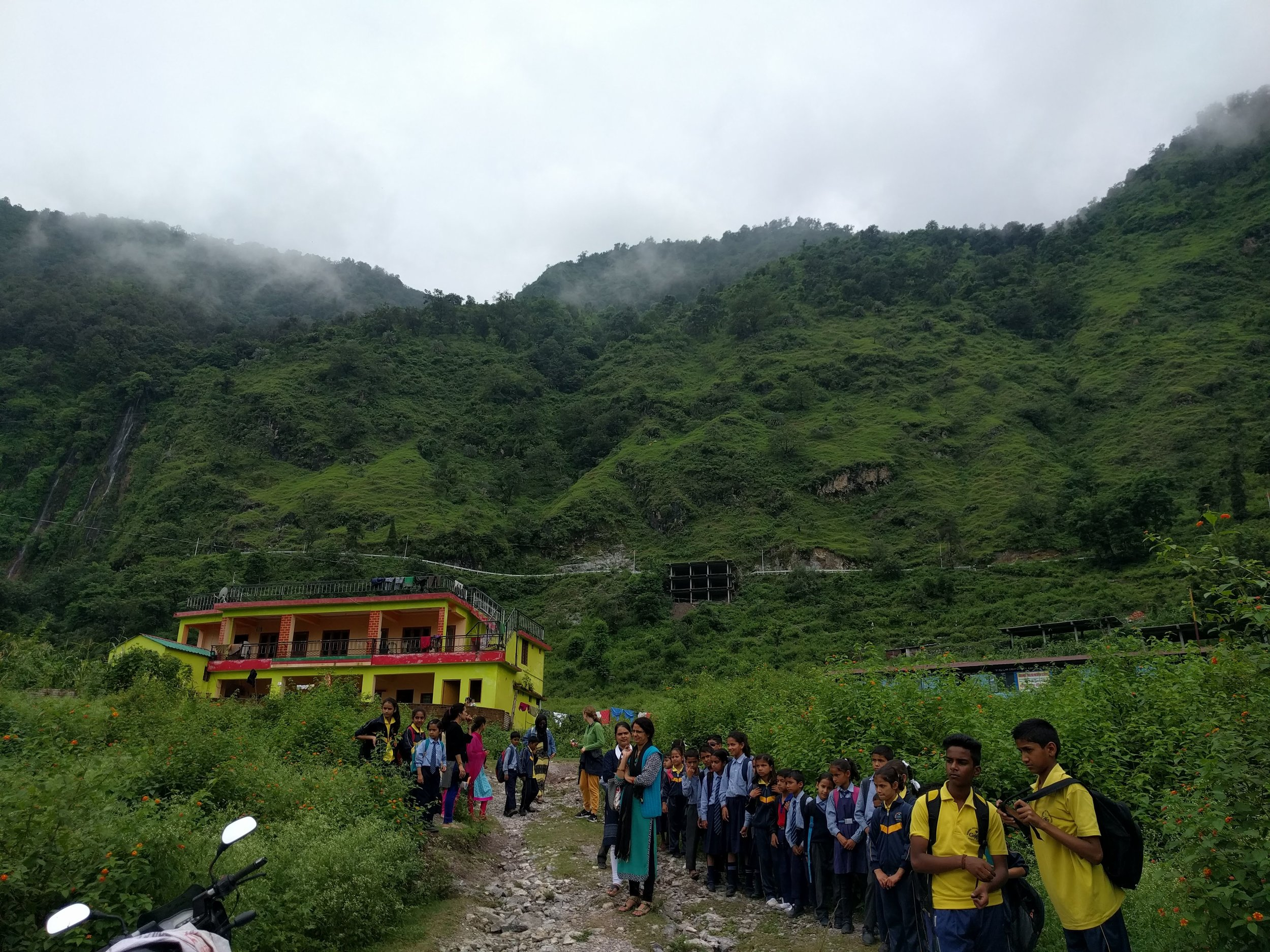 Students waiting for their buses home at the Garwhal English Medium School (GEMS). The small school building is barely visible above the plants on the right.