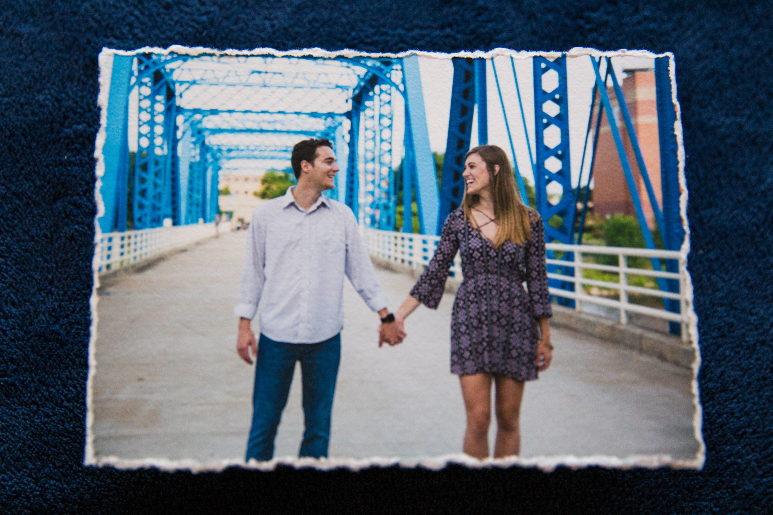 """A Grand Rapids couple hand-in-hand on the """"blue bridge"""". Shown here on a 5"""" x 7"""" deckled print, printed on museum-quality archival matte paper."""