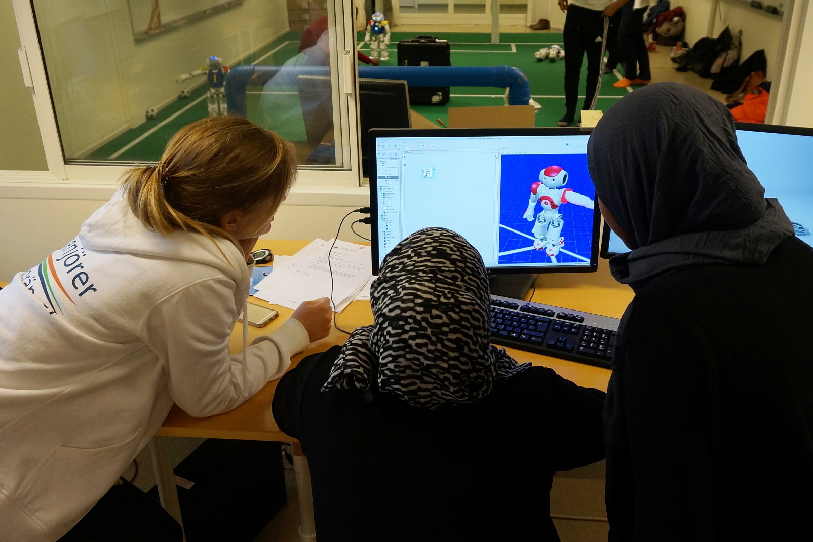 Two students Programming robots playing football with the supprt of a volunteer at linköping univeristy