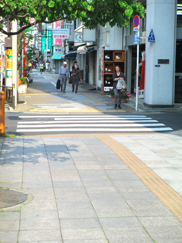 Textured guidestrips in Japan lead people along the sidewalk in addition to alerting of crosswalks