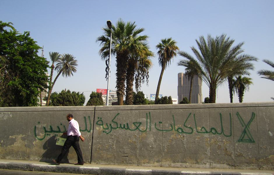 """A man walks by a property wall in Cairo that reads: """"No to Military trials against civilians"""". (Photo: Jenny Gustaffson) - Al Ahram"""
