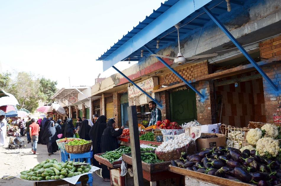 (Left) - Before and after market upgrade showing the center's wall and the market edges meet initially creating a conflict. Figure 11 (Right) - Mit 'Uqba Market after stalls addition along the youth center wall. (Photos: TADAMUN Website) (1)