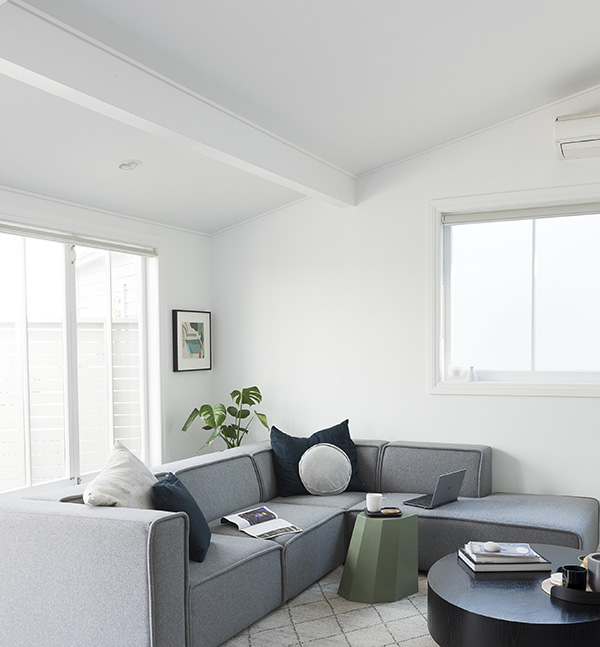 Light airy living area with white painted walls and grey lounger