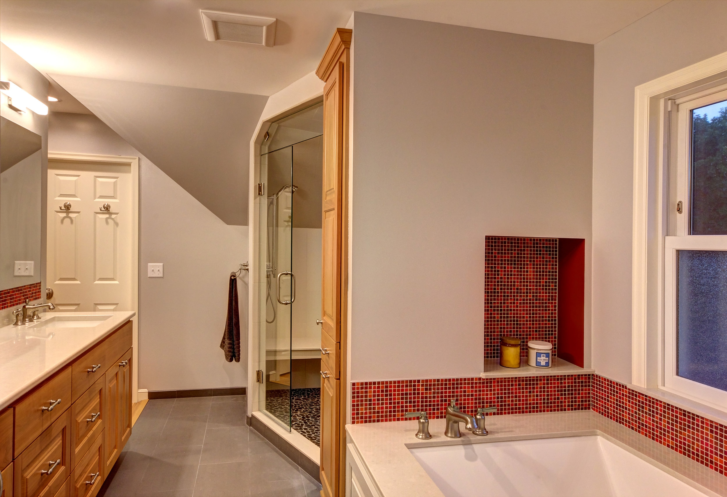 Shower with bench and frameless glass door.