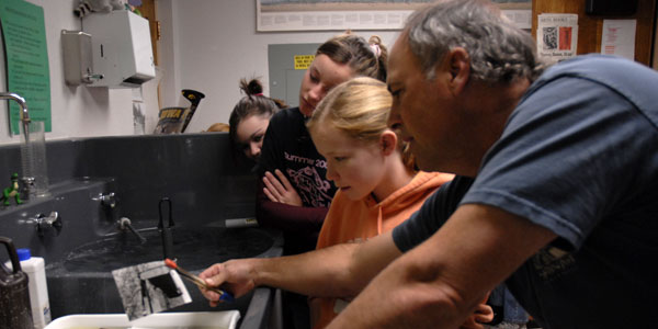 The artist instructs a group of students on the lost art of photographic printmaking. In a digital world, the unexpected beauty and simplicity of analog art is rare.