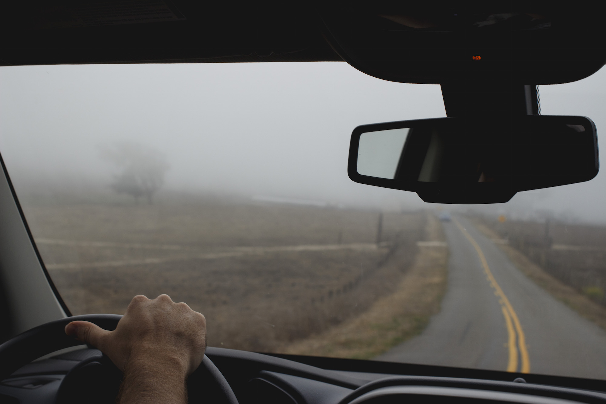hands-on-steering-wheel-foggy-road.jpg