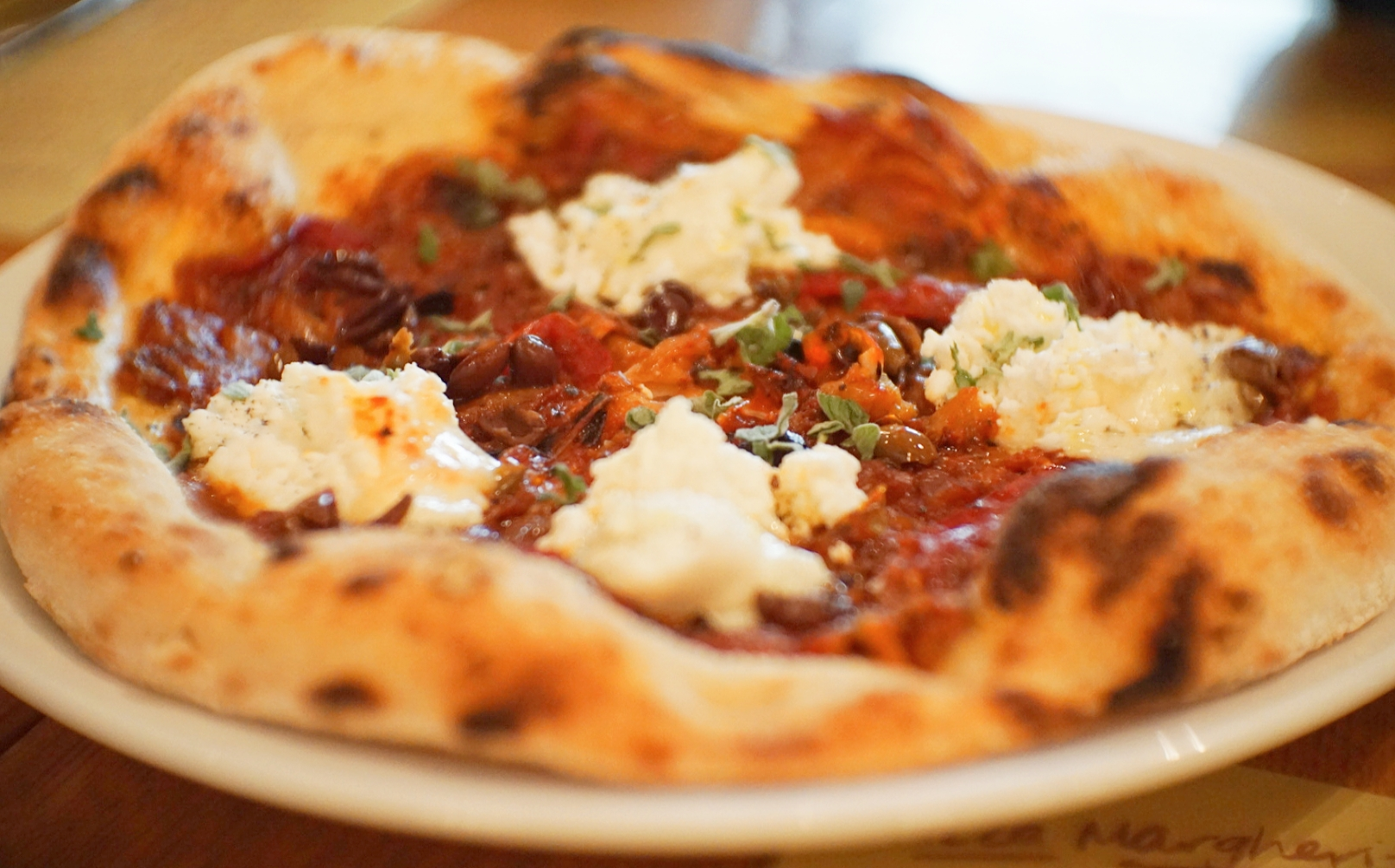 """Pizza topped with """"buricotta"""" - a burrata stuffed with ricotta instead of cream - sweet peppers and olives."""