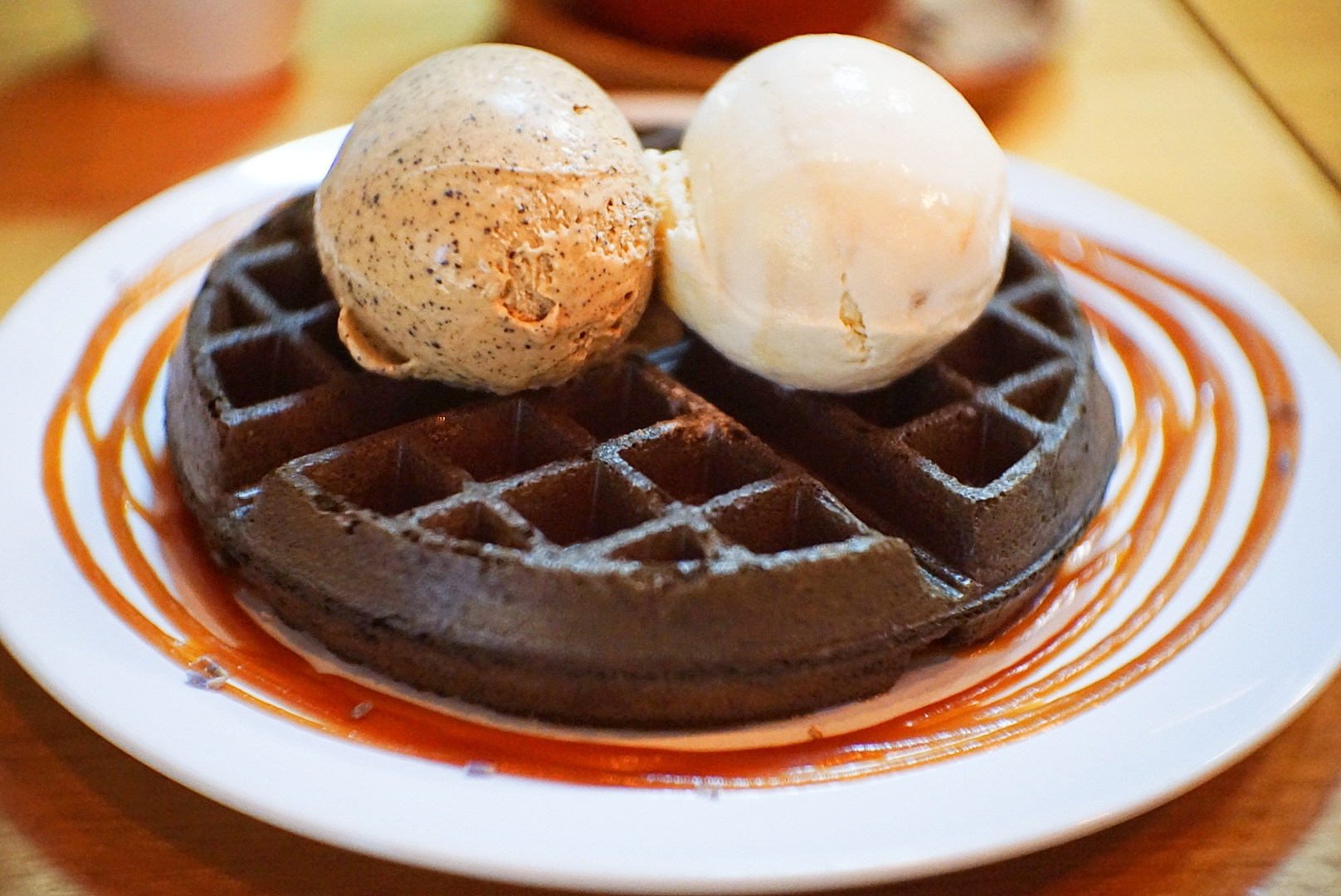 FATCAT charcoal waffles, with Butter Beer ice cream on the left and Butterscotch ice cream on the right. Served with salted caramel sauce and dried lavender garnish.