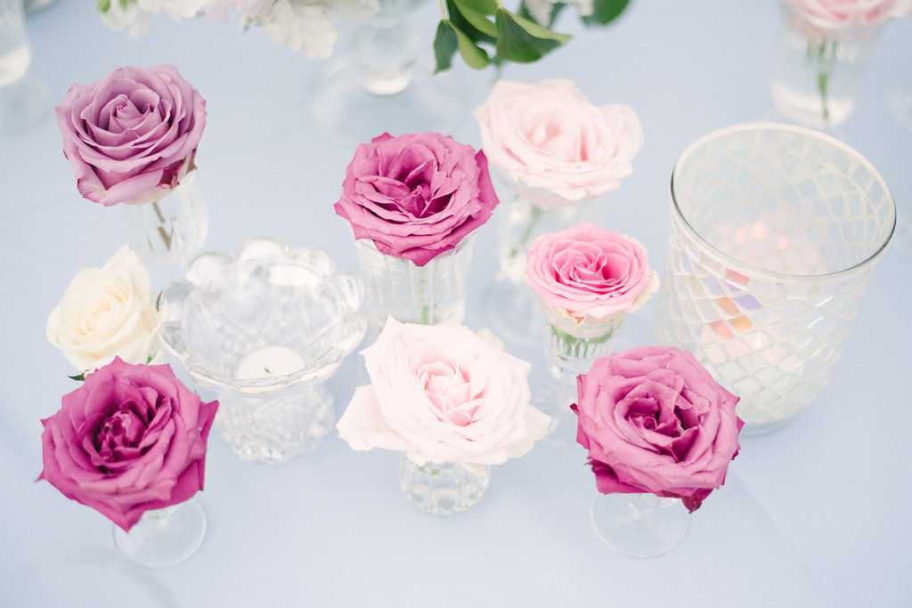 Australian grown roses in shimmering glass vases complete this wedding table setting