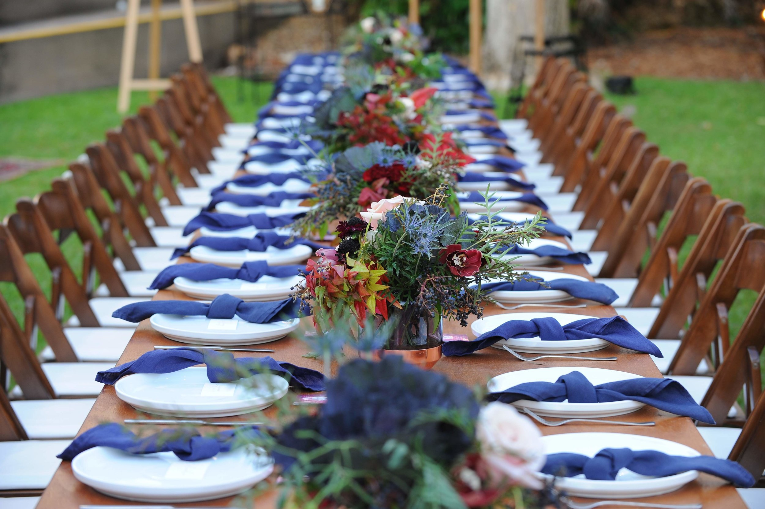 wedding table floral includes flower varieties dark purple kale, sea holly and roses