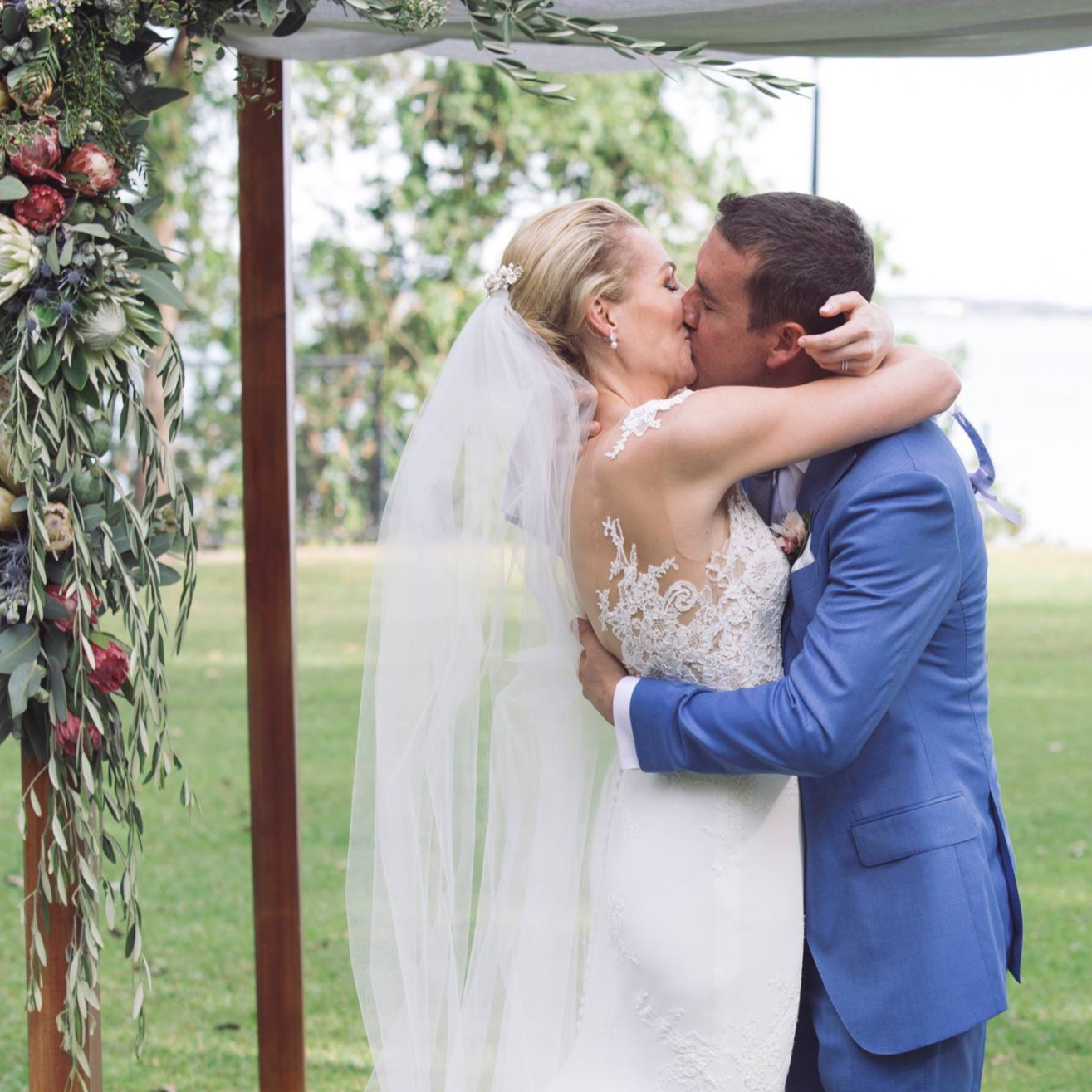 bride and groom kiss under ceremony arbour created by Darwin florist, Beija Flor