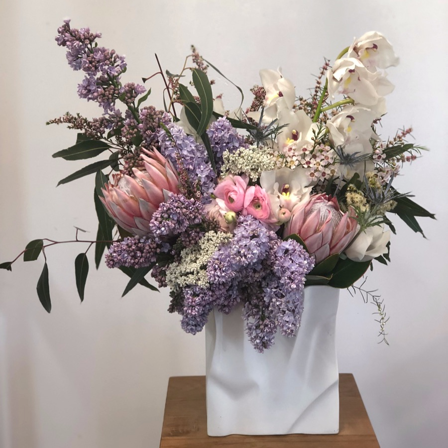 paper bag vase filled with king protea, lilac and orchids by Darwin florist Beija Flor