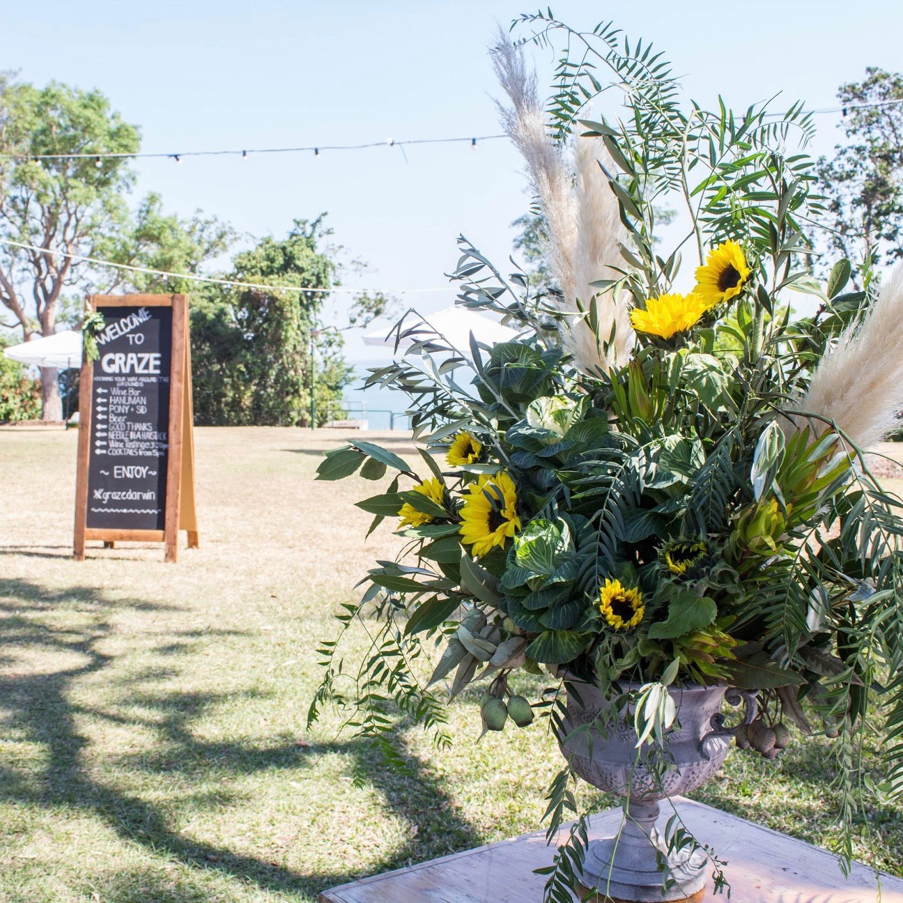 urn floral arrangement of sunflowers, pepper and pampas grass at Graze event in Darwin, NT by Darwin florist, Beija Flor