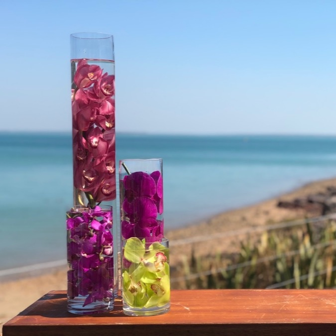 Submerged flower heads in cylinder vases, vibrant colours for a wedding at Darwins Pee Wees restaurant overlooking Fannie Bay.