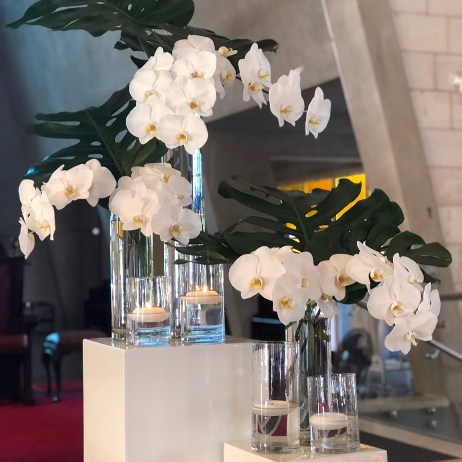 glass cylinder vases with white orchids and floating candles decorate a wedding ceremony at Darwins St Marys Star of the Sea Cathedral.
