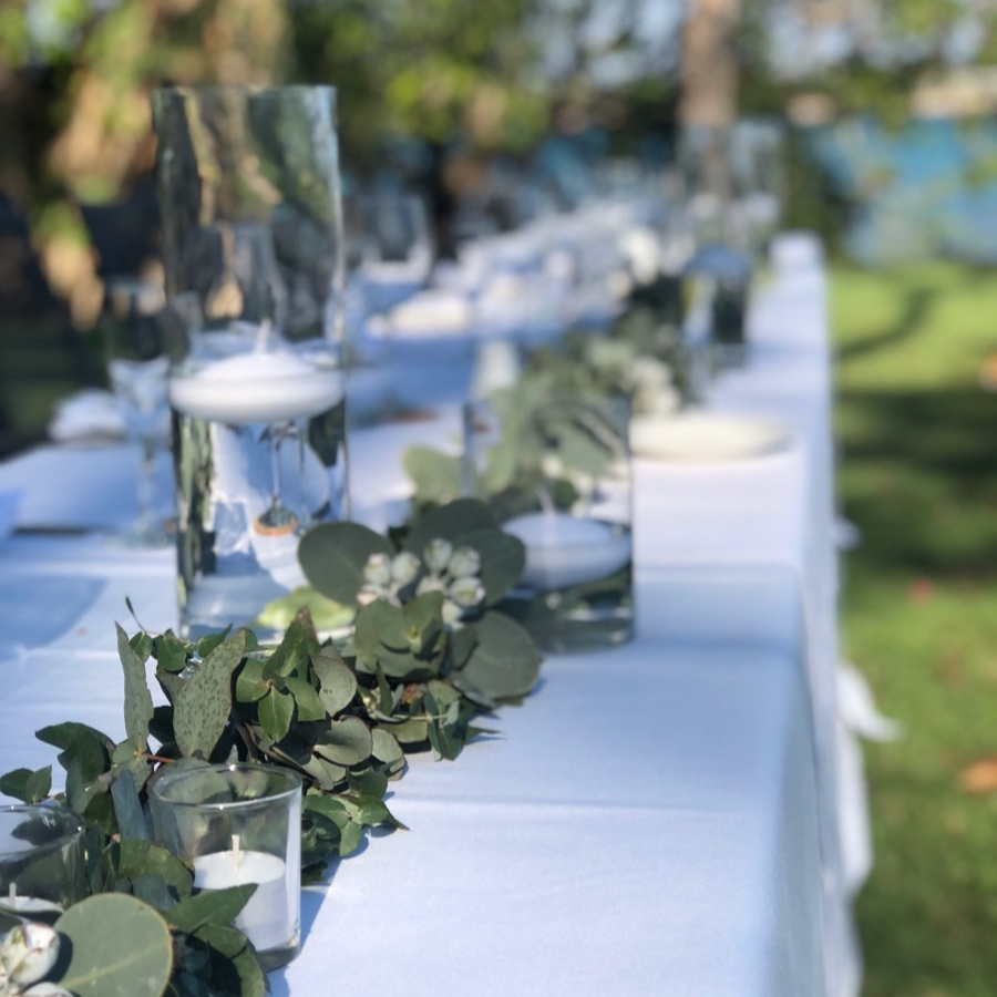 Fresh foliage garland of eucalyptus and gumnuts with floating candles adorns the bridal table at this Darwin wedding ceremony.