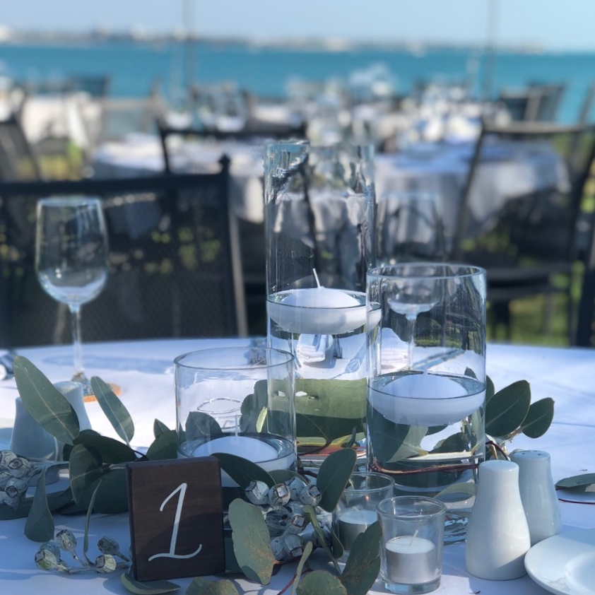 Simple candle tablescape with floating candles in glass cylinder vases surrounded by eucalyptus and gum nuts for a Darwin wedding reception overlooking Fannie Bay.