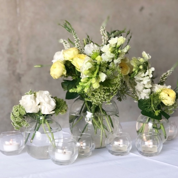 glass vases topped with fresh lemon and white flowers