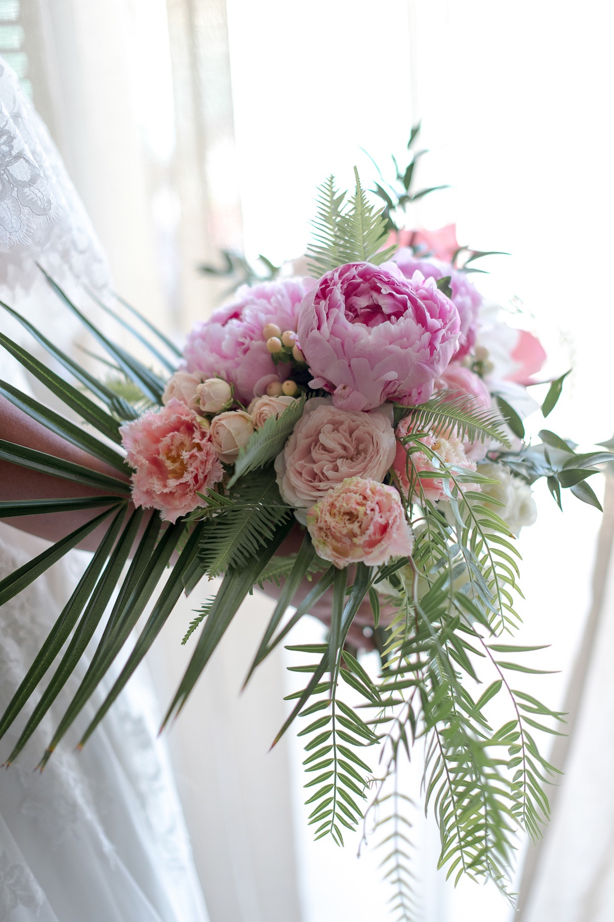 brides bouquet of Sarah Bernhardt peonies with frilled tulips and palms for a tropical feel.