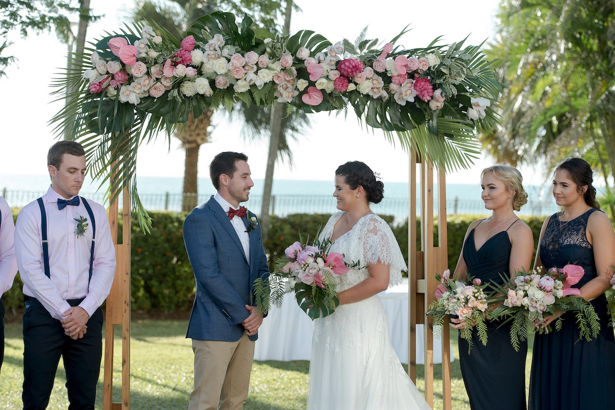 Wedding party under ceremony arbour clad with palm leaves and pink anthuriums.