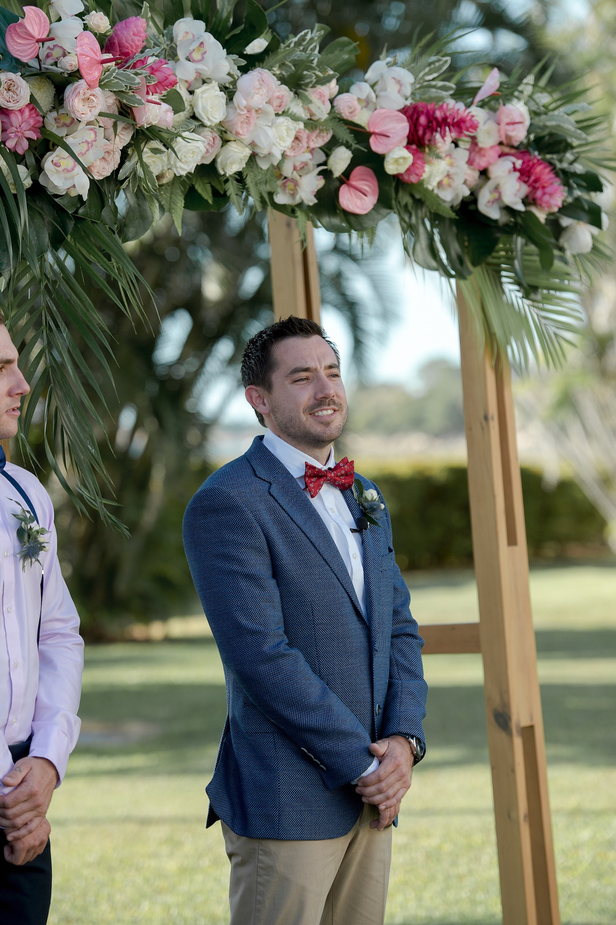 Wedding ceremony about to take place under tropical pink floral arbour. Groom awaits bride.