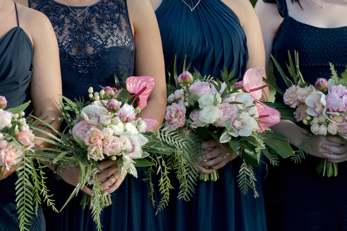 Bridesmaids in navy dresses with pink fresh flower bouquets