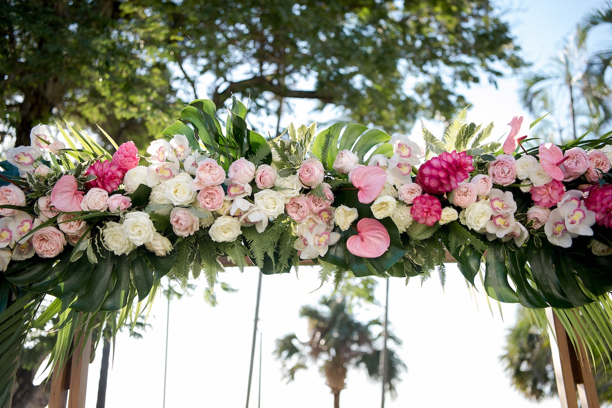 White roses, orchids, monstera leaves, fresh flowers for timber wedding arbour in Darwin.