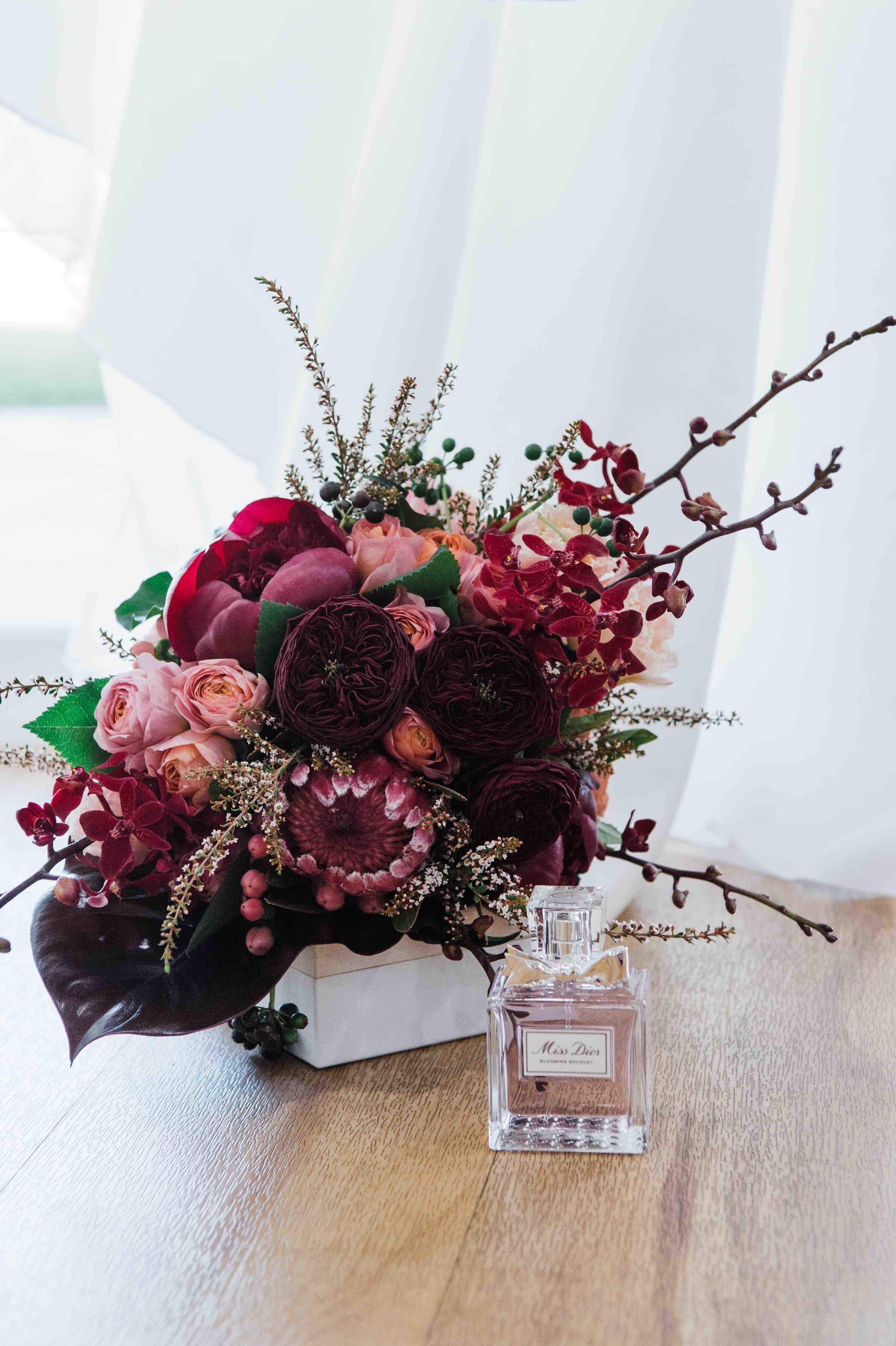 this brides bouquet has it all natives, peonies and tropical orchids and leaves