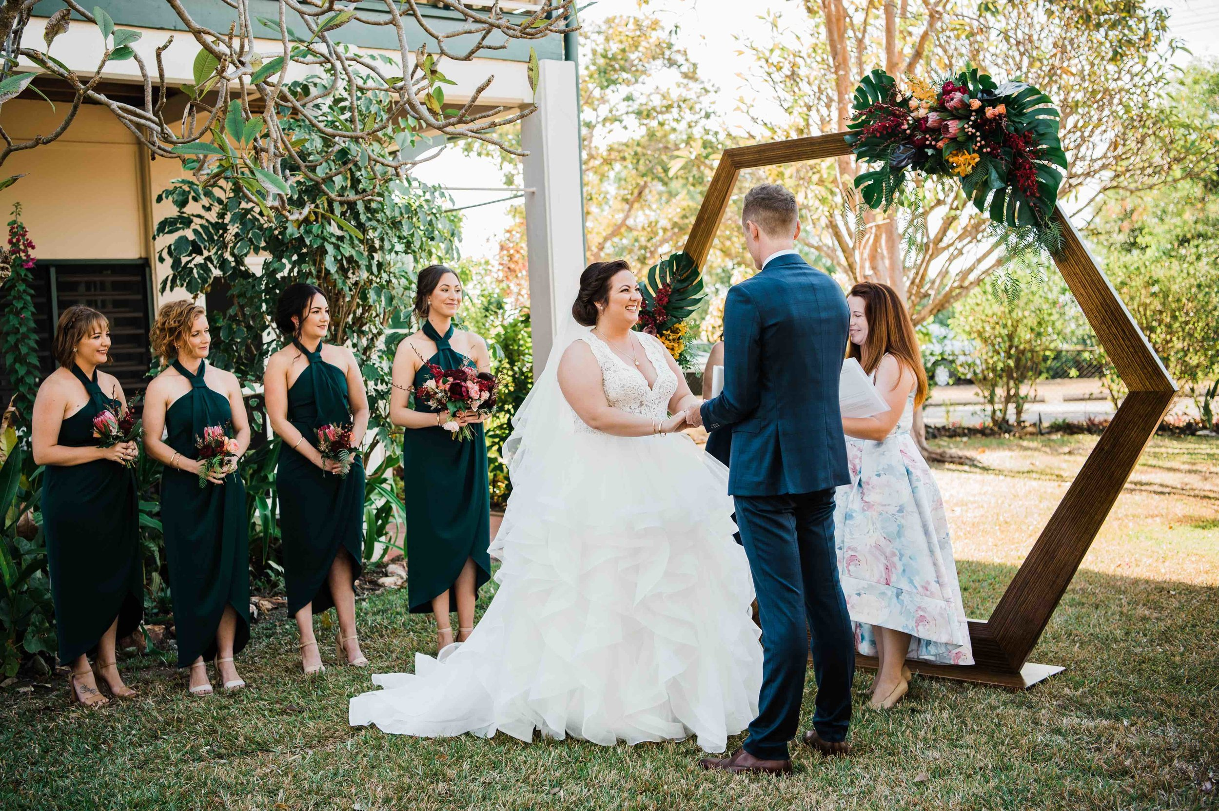 hexagonal arch ceremony backdrop dressed with native and tropical flowers