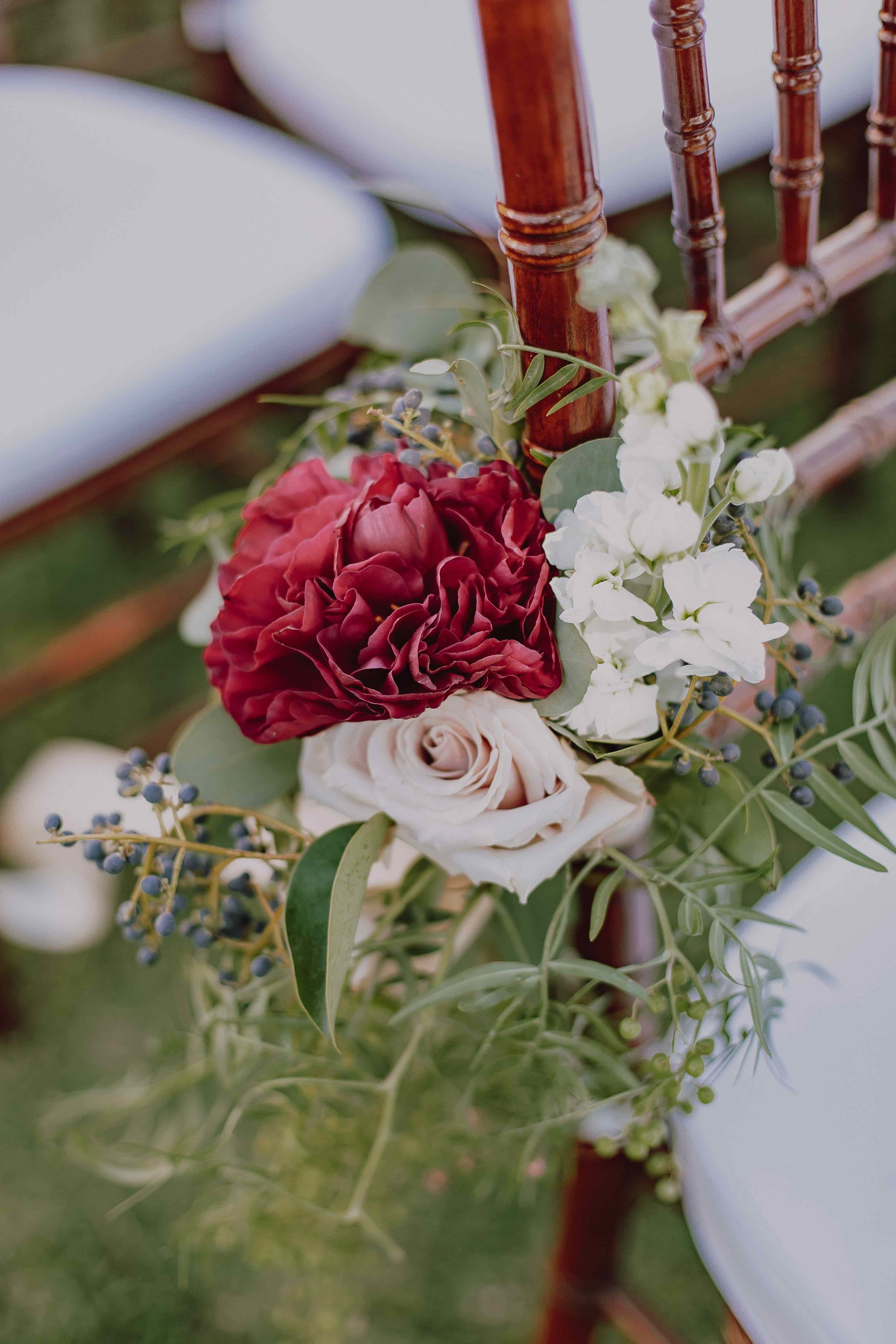 Red charm peonies and roses create a stunning aisle