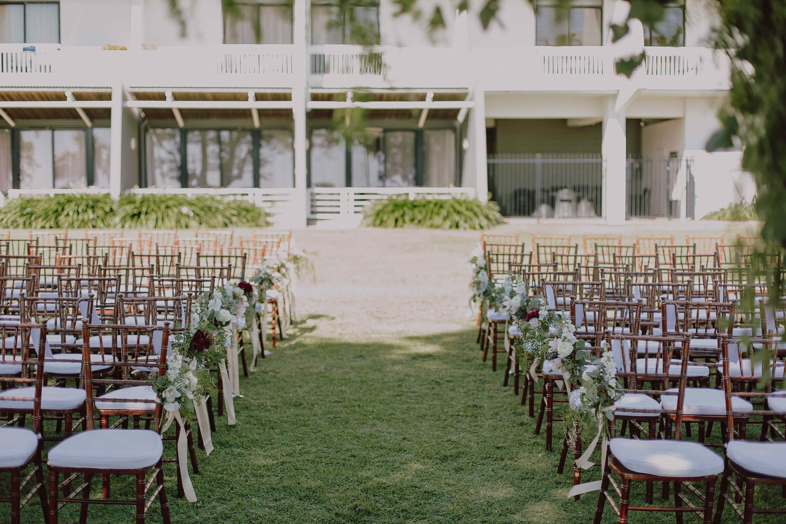 Rows of walnut Tiffany chairs on the lawns at Mindel Beach Casino and Resort for a Darwin wedding.