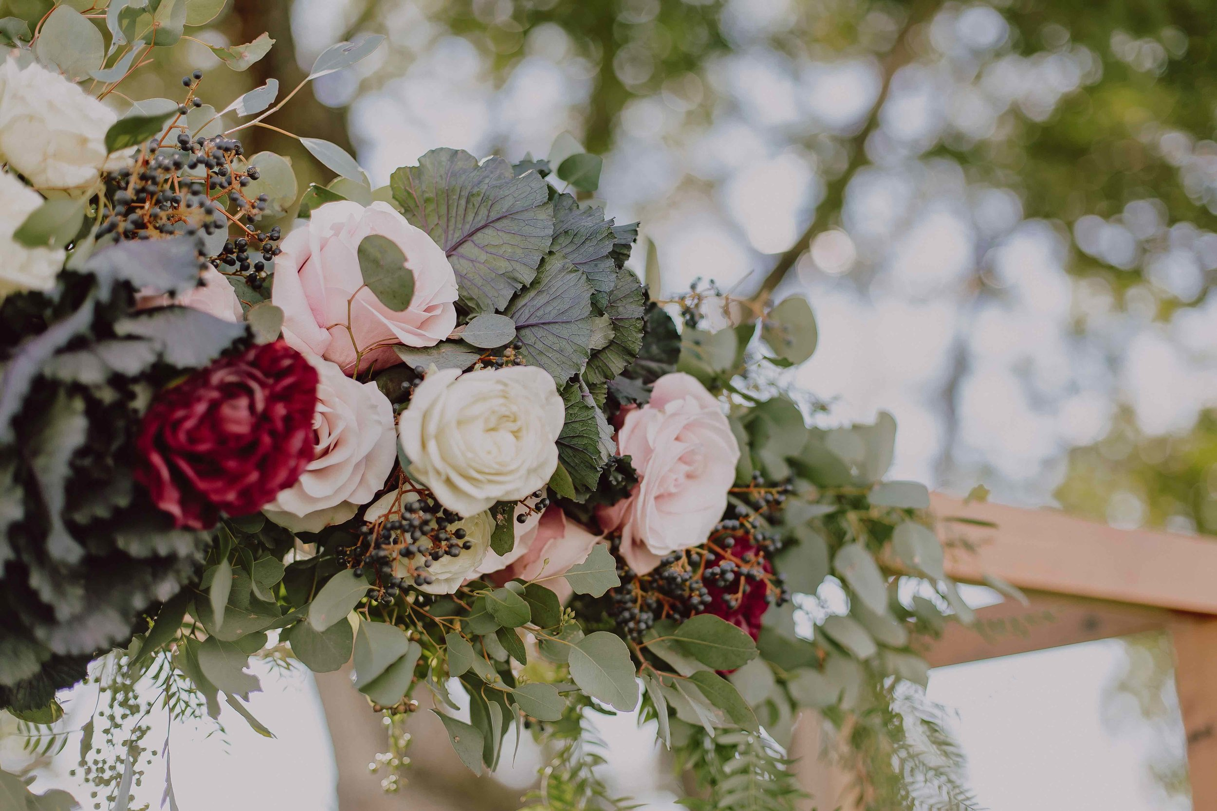 Red charm peonies with blush roses decorate this Darwin wedding ceremony.