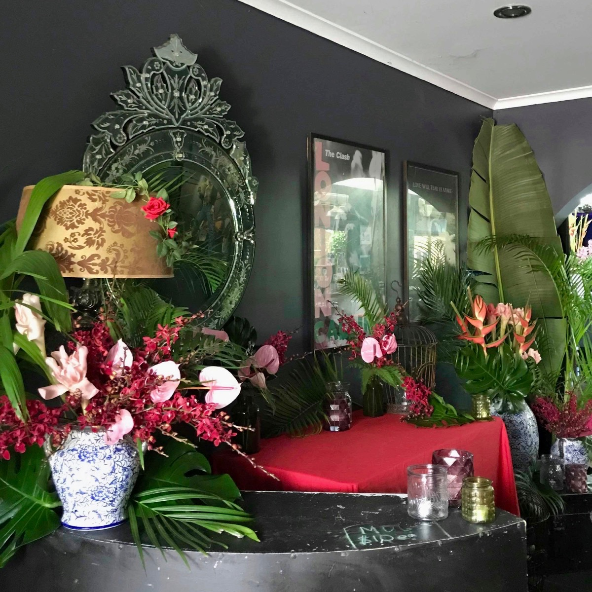 floral styling with tropical leaves green, blue and white vases and green glass votives at Darwin venue, The Railway Club