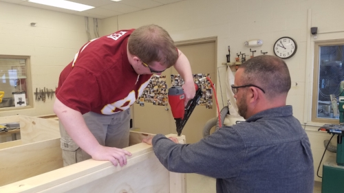 Building Management student and teacher work together on a clothing armoire.