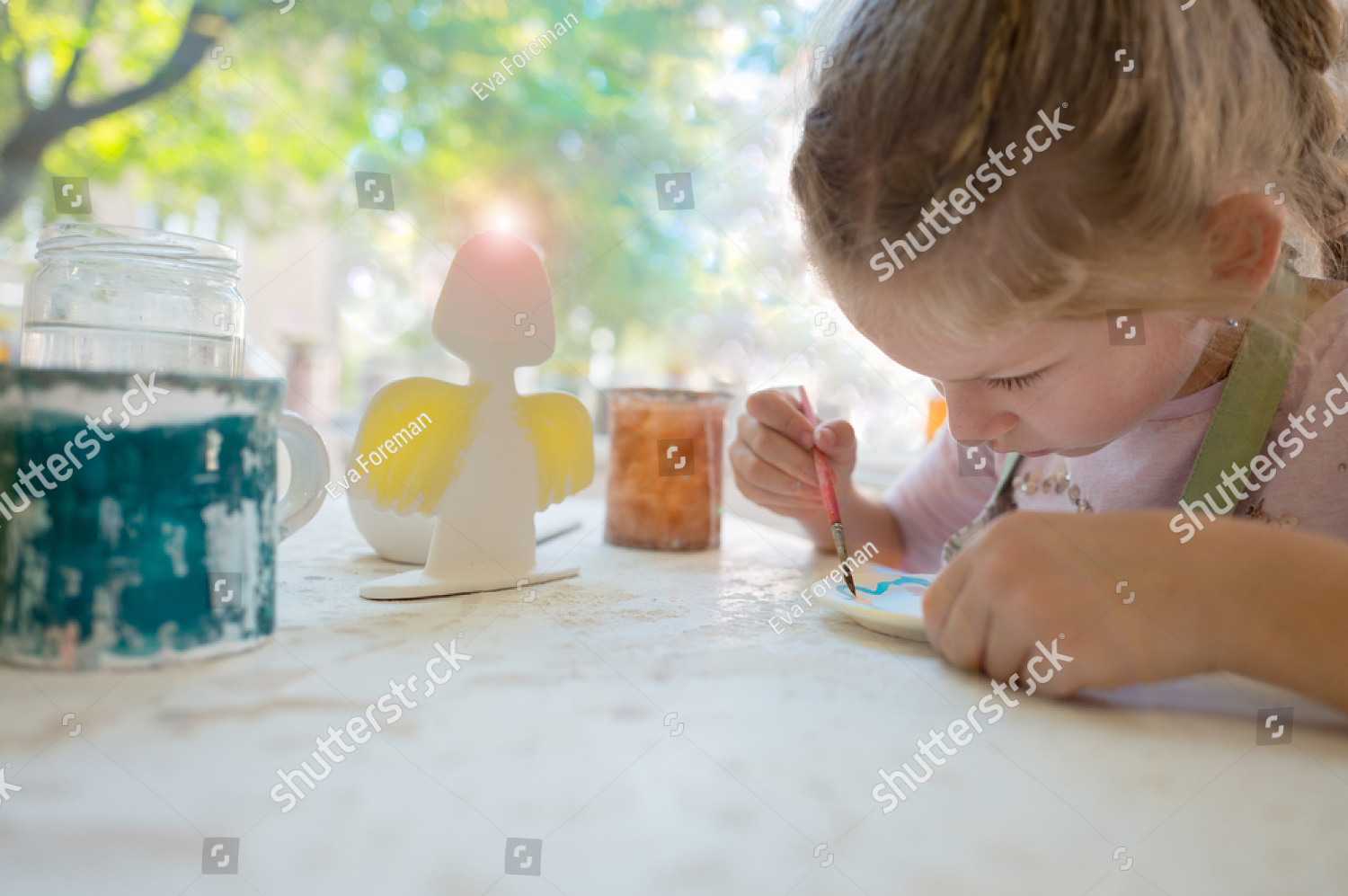stock-photo-young-girl-painting-in-pottery-workshop-using-colourful-paints-and-brush-725047486.jpg