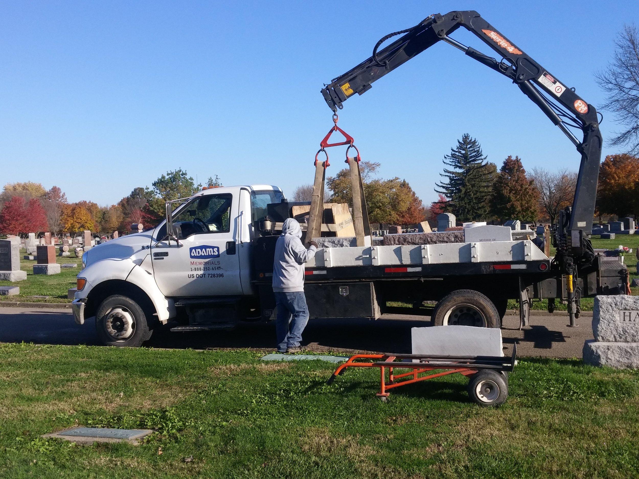 Unloading monument base with crane