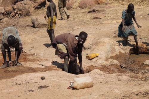 Children drinking from hand-dug wells
