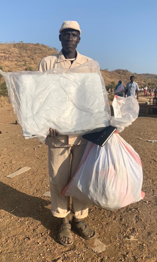 December distribution - man with SAP Bible and Tarp.jpg