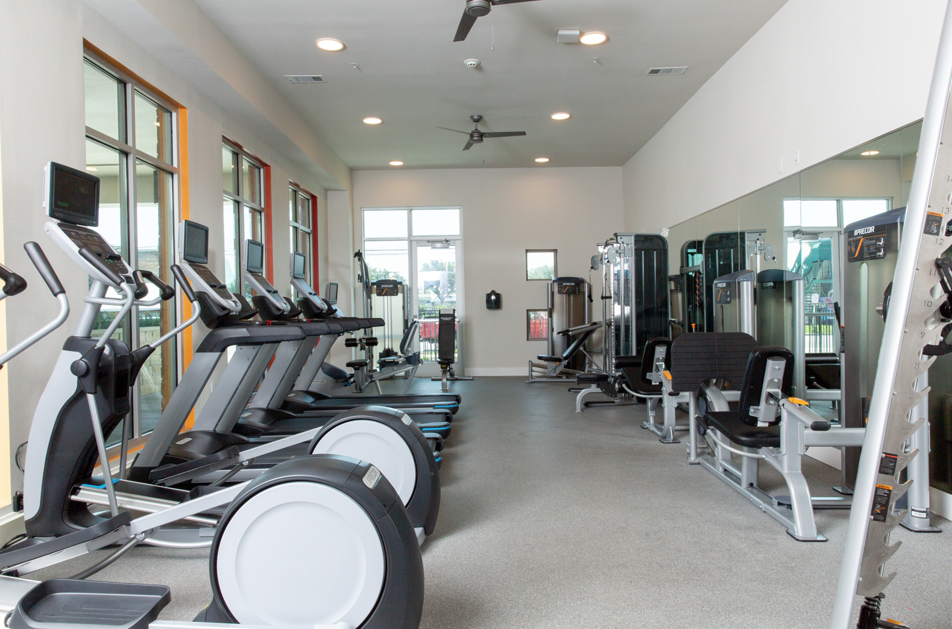 Interior of 24-hour fitness center. FLORA Apartments is a modern and upscale development in Austin, Texas by JCI Residential. Located on Middle Fiskville Road in the North Loop neighborhood in north central Austin. Efficiencies, one-bedroom, and two-bedrooms units. Pet-friendly.