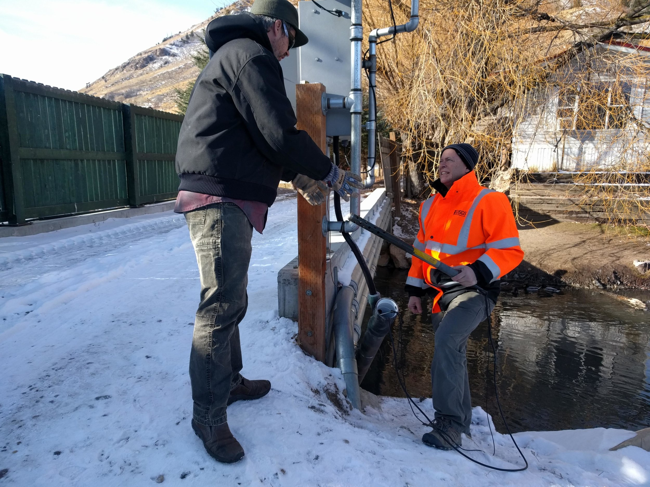 Carlin Girard of Teton Conservation District and Chris Ellison of USGS checking on the turbidity monitor in Flat Creek.