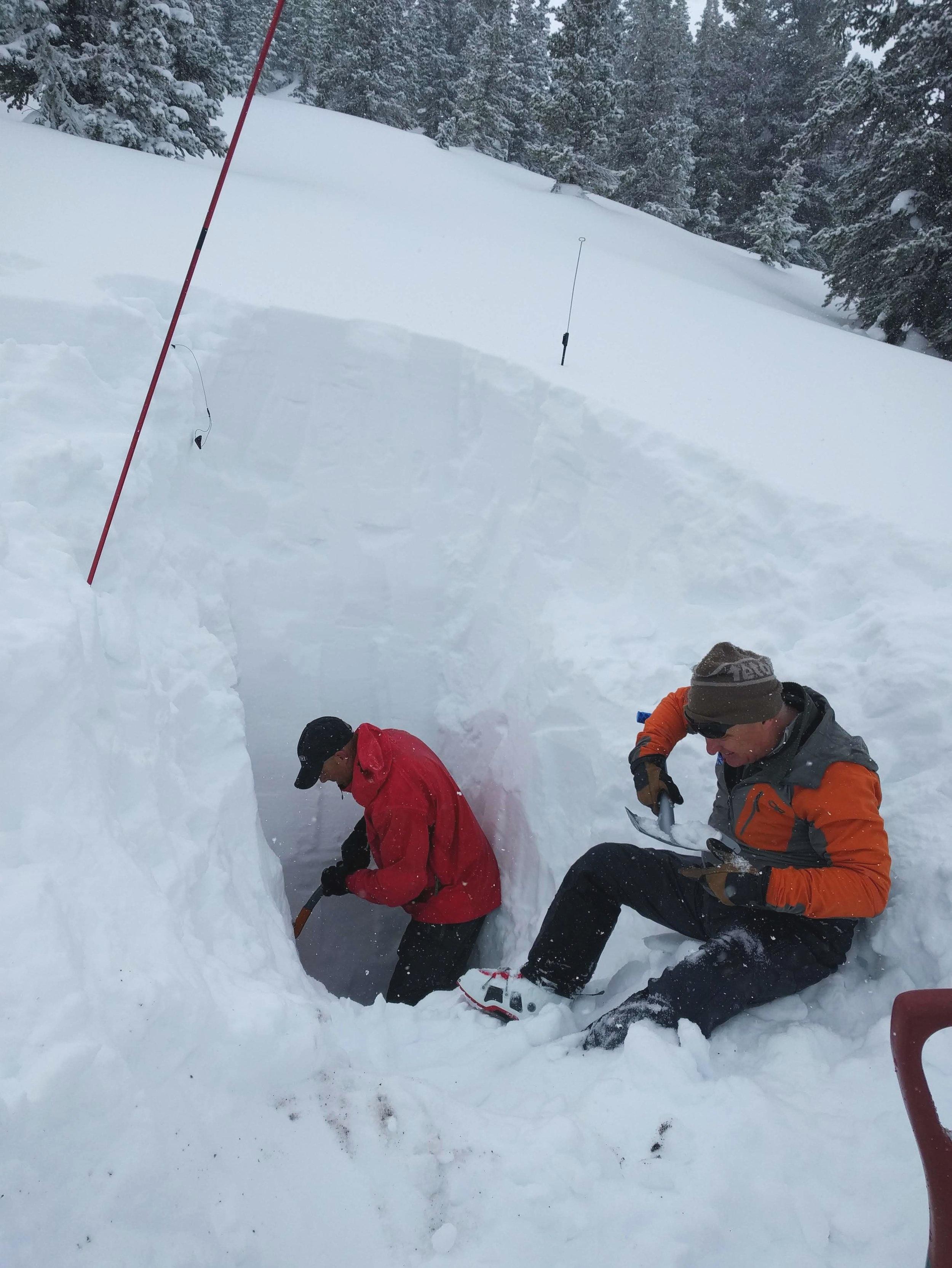 Robb shovels and Bob examines snow grain types.
