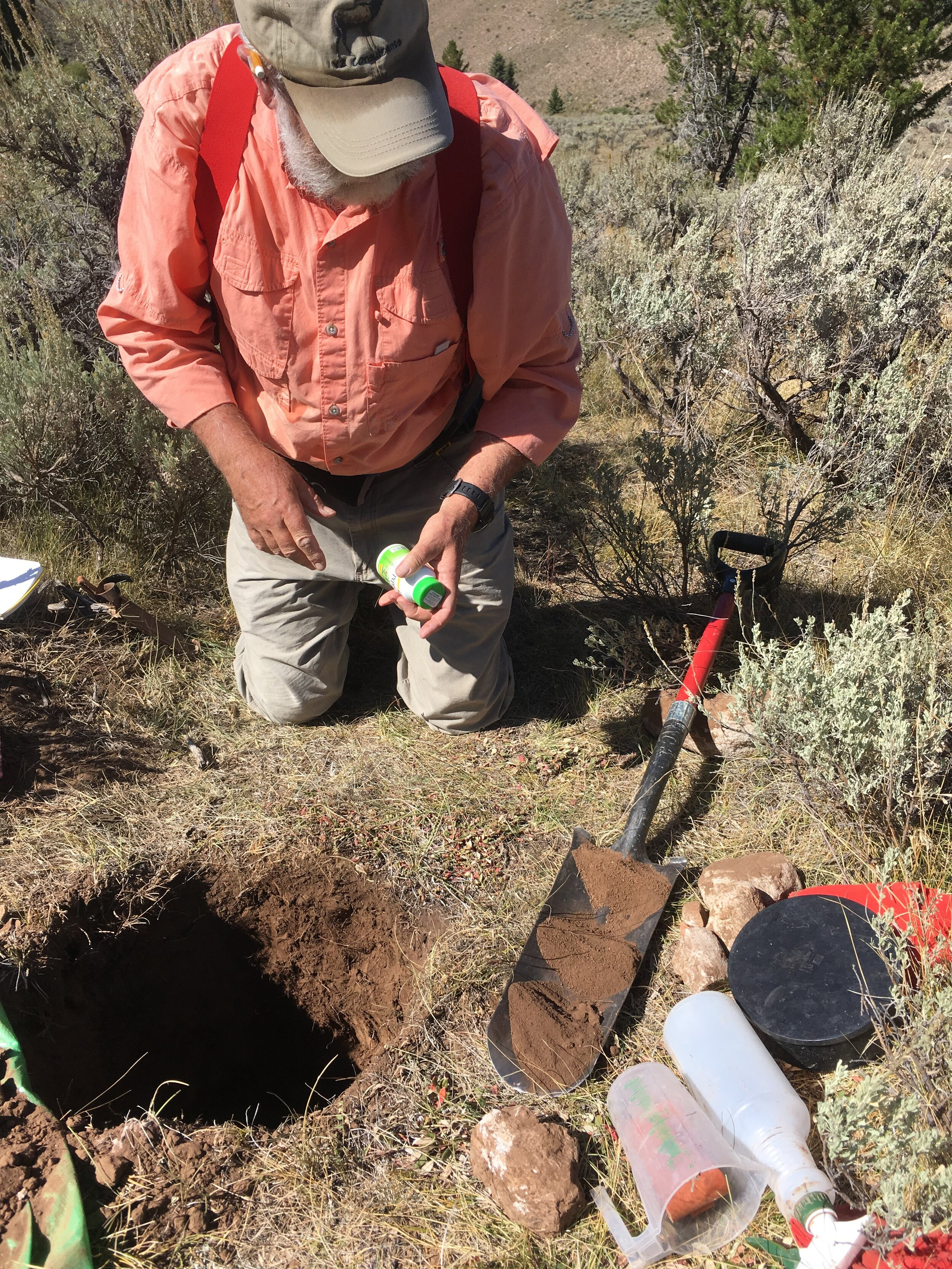 Dr. Chuck Butterfield examining soil from different horizons within the sample hole.