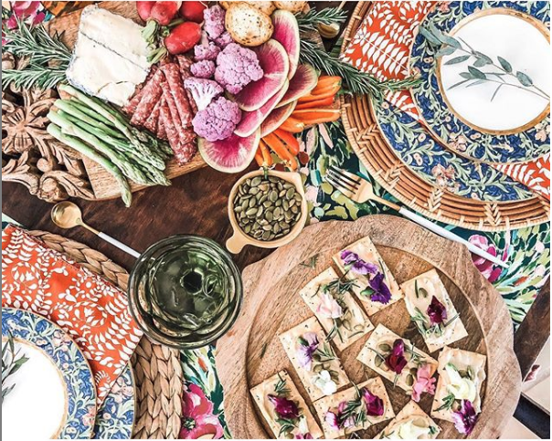 Maximalist Charcuterie Table spread with veggies, hummas and edible flowers. Featuring Bari J place settings